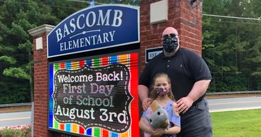John Barrett and his daughter Autumn pose for photos outside Bascomb Elementary School in Woodstock, Ga., Thursday, July 23, 2020.