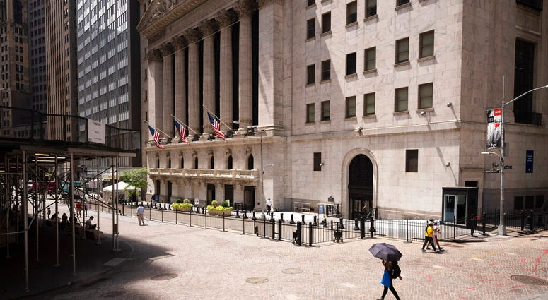 FILE - People pass the New York Stock Exchange, Thursday, July 30, 2020.