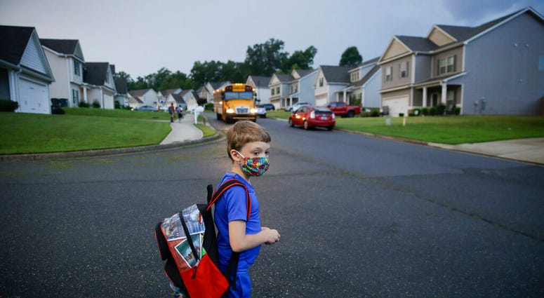 Paul Adams, 7, waits at the bus stop for the first day of school on Monday, Aug. 3, 2020, in Dallas, Ga.   (AP Photo/Brynn Anderson)
