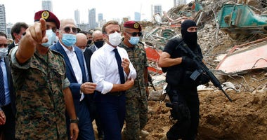 French President Emmanuel Macron, center, visits the devastated site of the explosion at the port of Beirut, Lebanon, Thursday Aug.6, 2020.