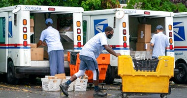 In this July 31, 2020, file photo, letter carriers load mail trucks for deliveries at a U.S. Postal Service facility in McLean, Va. (AP Photo/J. Scott Applewhite, File)