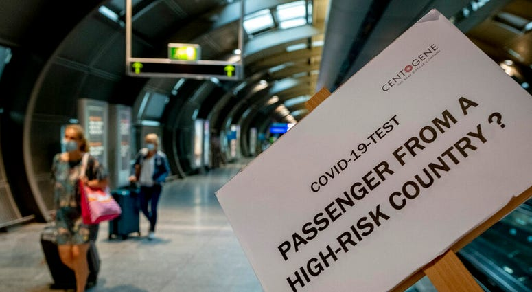 A sign helps passengers to find the Cover-19 test center at the airport in Frankfurt, Germany, Saturday, Aug. 8, 2020. From Saturday on Covid-19 tests are mandatory for passengers coming from a high-risk-country.