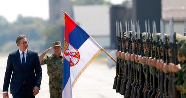 FILE - In this Tuesday, Aug. 21, 2018 file photo, Serbian President Aleksandar Vucic, left, reviews an honor guard on the tarmac at Batajnica, military airport near Belgrade, Serbia. (AP Photo/Darko Vojinovic)