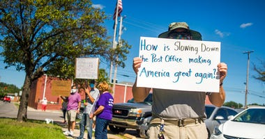 Eric Severson holds a sign as a few dozen people gather in front of the United States Post Office on Rodd St.  in Midland, Mich. (Katy Kildee/Midland Daily News via AP)