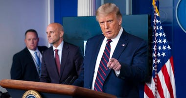 President Donald Trump speaks, accompanied by Food and Drug Administration Commissioner Dr. Stephen Hahn, center, during a media briefing in the James Brady Briefing Room of the White House, Sunday, Aug. 23, 2020, in Washington.