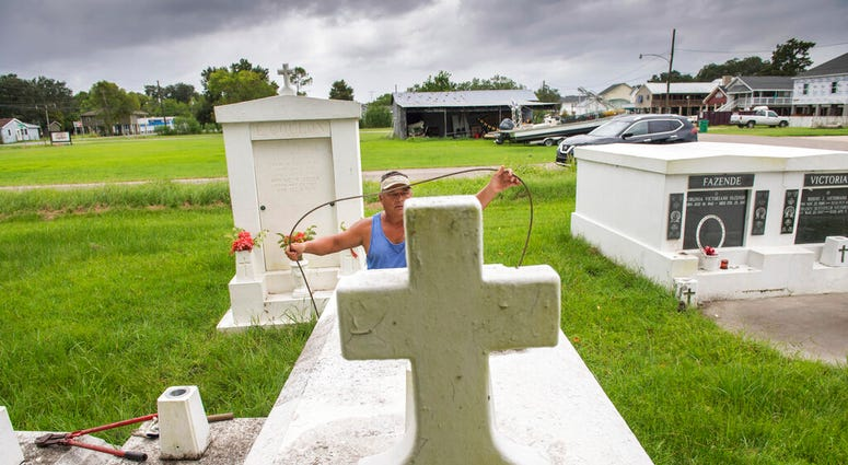 Jerry Parria uses steel cable and metal anchors to tie down four tombs belonging to his grandparents and uncles in a small cemetery near Lafitte, La.  (Chris Granger/The Times-Picayune/The New Orleans Advocate via AP)