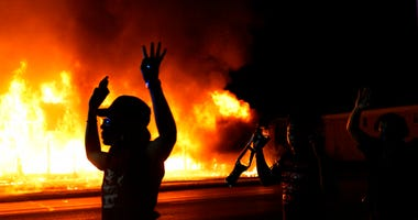 Protesters walk past police with their arms up, late Monday, Aug. 24, 2020, in Kenosha, Wis., as a building burns in the background. Protests have erupted following the police shooting of Jacob Blake a day earlier. (AP Photo/David Goldman)