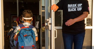 A staff member holds the door open for kids on the first day of school at Goodwin Frazier Elementary School in New Braunfels, Texas on Tuesday, Aug. 25, 2020. (Mikala Compton/Herald-Zeitung via AP)