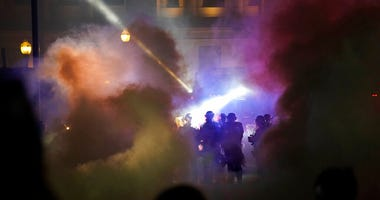 Police in riot gear clear the area in front of Kenosha County Courthouse during clashes with protesters late Tuesday, Aug. 25, 2020, in Kenosha, Wis. (AP Photo/David Goldman)