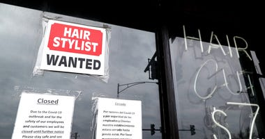 In this April 30 ,2020 file photo, a barber shop shows closed and hiring sign during the COVID-19 in Chicago. (AP Photo/Nam Y. Huh, File)