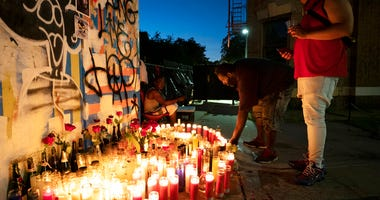 Friends of Wesley Green light candles at a sidewalk memorial for him, July 28, 2020 in the Ditmas Park neighborhood of New York. (AP Photo/Mark Lennihan)