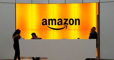 FILE - In this Feb. 14, 2019 file photo, people stand in the lobby for Amazon offices in New York. While other companies are shrinking, Amazon is growing. (AP Photo/Mark Lennihan, File)