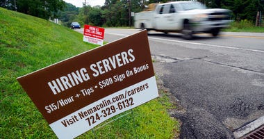 FILE - In this Wednesday, Sept. 2, 2020, file photo help wanted signs for servers and cooks at Nemacolin Woodlands Resort and Spa are displayed along route 40 at the entrance to the resort in Farmington, Pa.