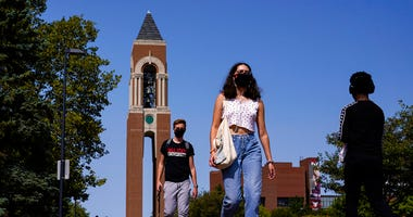 Masked students walk through the campus of Ball State University in Muncie, Ind., Thursday, Sept. 10, 2020. (AP Photo/Michael Conroy)