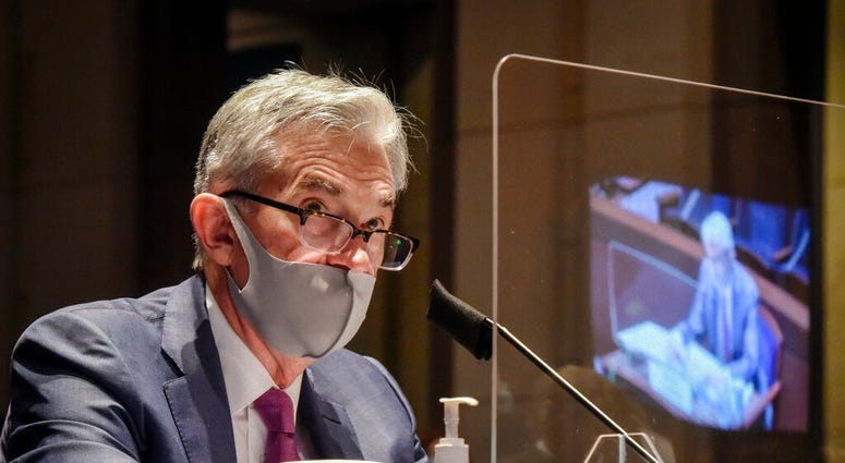 In this June 30, 2020, file photo Federal Reserve Board Chairman Jerome Powell, reflected in the sneeze guard set up between himself and members of the House Committee on Financial Services. (Bill O'Leary/The Washington Post via AP, Pool)