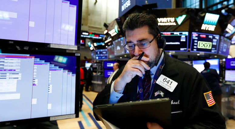 In this Jan. 27, 2020, file photo, trader Michael Capolino works on the floor of the New York Stock Exchange. (AP Photo/Richard Drew, FIle)