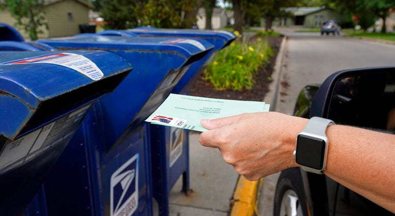 FILE - In this Tuesday, Aug. 18, 2020, file photo, a person drops applications for mail-in-ballots into a mailbox in Omaha, Neb. (AP Photo/Nati Harnik, File)