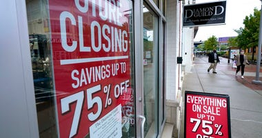 Passersby walk past a business storefront with store closing and sale signs, Wednesday, Sept. 2, 2020, in Dedham, Mass.  (AP Photo/Steven Senne)