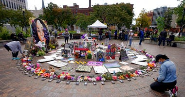 A women kneels in front of a makeshift memorial in honor of Breonna Taylor, at Jefferson Square Park, Thursday, Sept. 24, 2020, in Louisville, Ky. (AP Photo/Darron Cummings)