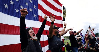 Members of the Proud Boys cheer on stage as they and other right-wing demonstrators rally, Saturday, Sept. 26, 2020, in Portland, Ore. (AP Photo/John Locher)