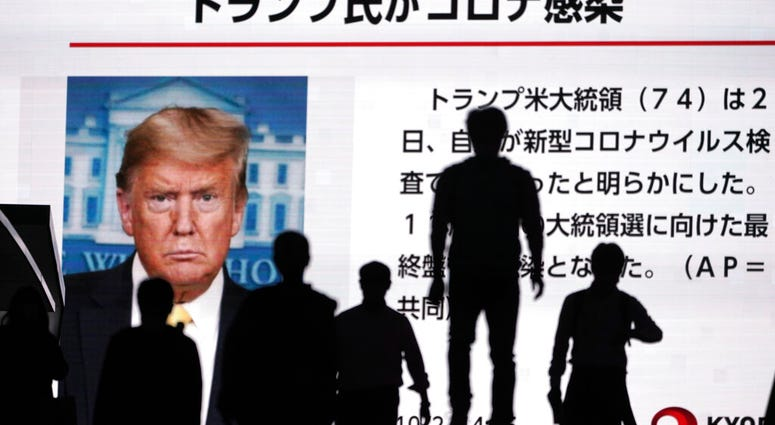 People walk past a screen showing the news report that President Donald Trump has tested positive for the coronavirus, Friday, Oct. 2, 2020, in Tokyo. (AP Photo/Eugene Hoshiko)