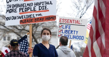 In this April 24, 202, file photo, a nurse demonstrating in favor of business closures is surrounded by demonstrators against Gov. Tony Evers' restrictions on daily life due to the coronavirus pandemic at the Capitol in Madison, Wis.