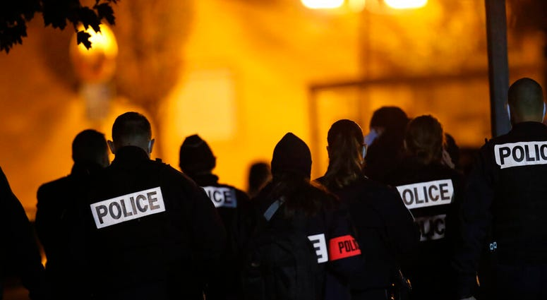 French police officers gather outside a high school after a history teacher who opened a discussion with students on caricatures of Islam's Prophet Muhammad was beheaded, Friday, Oct. 16, 2020 in Conflans-Saint-Honorine.(AP Photo/Michel Euler)