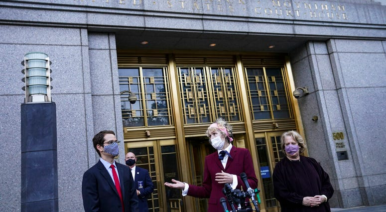 E. Jean Carroll, center, who says President Donald Trump raped her in the 1990s, speaks to reporters as she leaves the Daniel Patrick Moynihan United States Courthouse following a hearing in her defamation lawsuit against Trump, Wednesday, Oct. 21, 2020.