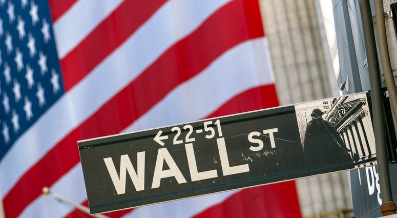 In this Monday, Sept. 21, 2020, file photo, a Wall Street street sign is framed by a giant American flag hanging on the New York Stock Exchange in New York. (AP Photo/Mary Altaffer, File)
