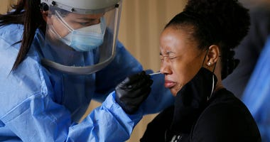Sasha Jacquez tests The University of Texas at El Paso student Ariona Gill for coronavirus Friday, Oct. 16, 2020, at the UTEP Fox Fine Arts Center in El Paso, Texas. (Mark Lambie/The El Paso Times via AP)