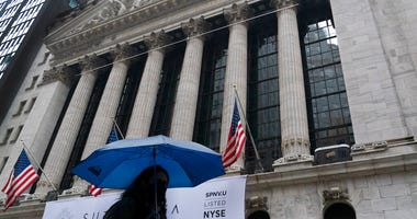 A woman with an umbrella passes the New York Stock Exchange, Monday, Oct. 26, 2020. (AP Photo/Mark Lennihan)