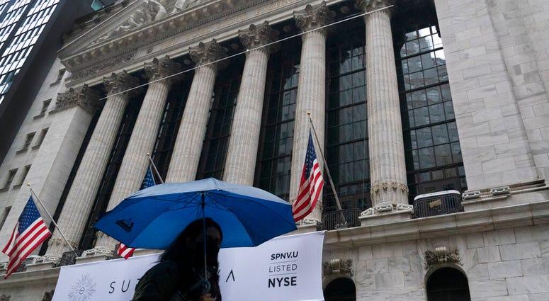 A woman with an umbrella passes the New York Stock Exchange, Monday, Oct. 26, 2020. (AP Photo/Mark Lennihan)
