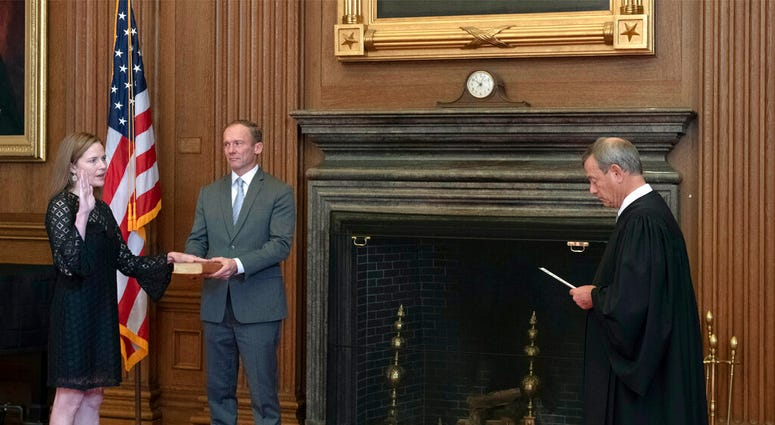 Chief Justice John G. Roberts, Jr., right, administers the Judicial Oath to Judge Amy Coney Barrett in the East Conference Room of the Supreme Court Building, Tuesday, Oct. 27, 2020, in Washington.