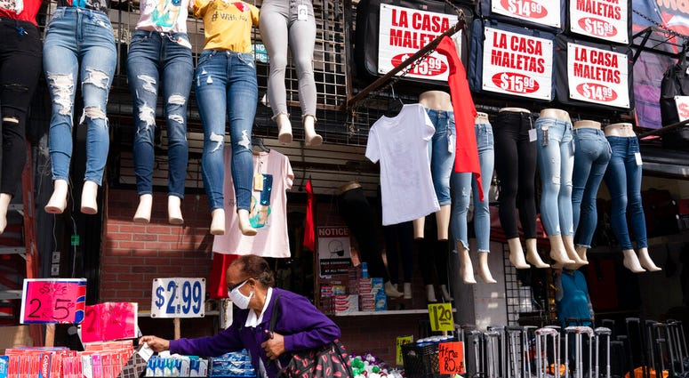 In this Sept. 25, 2020 file photo, a woman shops at a clothing store in New York. (AP Photo/Mark Lennihan, File)
