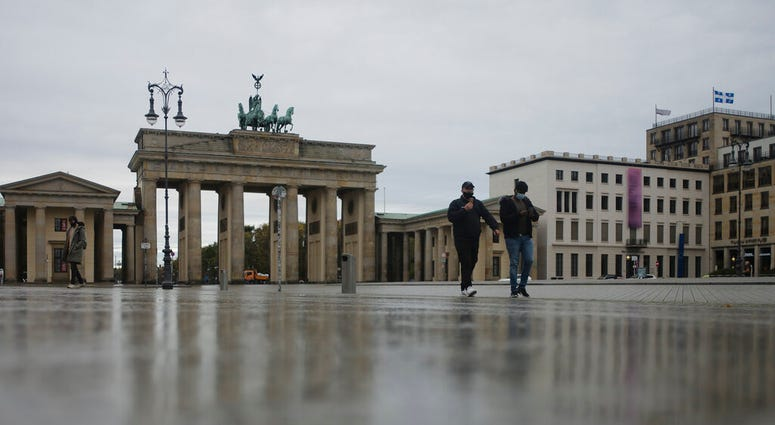 Two men with face maskes cross the desrted Pariser Platz in front of the Brandenburg Gate, a tourist highlight, in Berlin, Germany, Monday, Nov. 2, 2020. (AP Photo/Markus Schreiber)