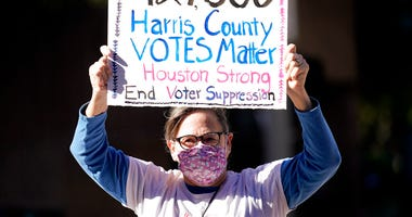 Demonstrator Gina Dusterhoft holds up a sign as she walks to join others standing across the street from the federal courthouse in Houston, Monday, Nov. 2, 2020.   (AP Photo/David J. Phillip)