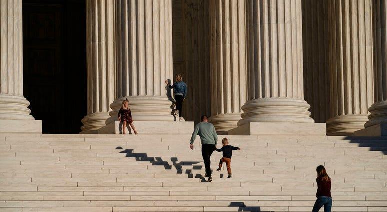 A family visits the Supreme Court in Washington, Wednesday, Nov. 4, 2020. (AP Photo/J. Scott Applewhite)