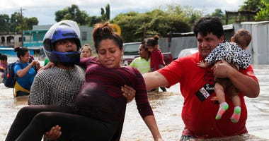 A pregnant woman is carried out of an area flooded by water brought by Hurricane Eta in Planeta, Honduras, Thursday, Nov. 5, 2020.  (AP Photo/Delmer Martinez)