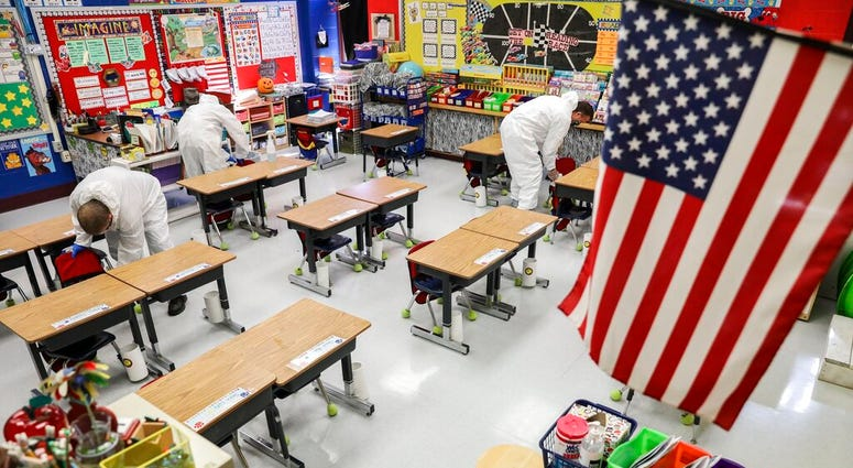 In this Nov. 5, 2020, file photo, custodial workers clean a classroom at Richard A. Simpson Elementary School in Arnold, Mo. (Colter Peterson/St. Louis Post-Dispatch via AP, File)