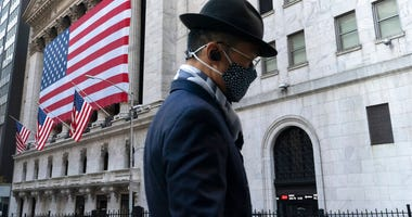 A man wearing a mask passes the New York Stock Exchange, Monday, Nov. 16, 2020, in New York. Stock markets are rallying on news that a second coronavirus vaccine shows promise. (AP Photo/Mark Lennihan)