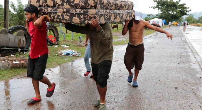 Neighbors help each other as they evacuate the area before Hurricane Iota makes landfall in San Manuel Cortes, Honduras, Monday, November 16, 2020. (AP Photo/Delmer Martinez)