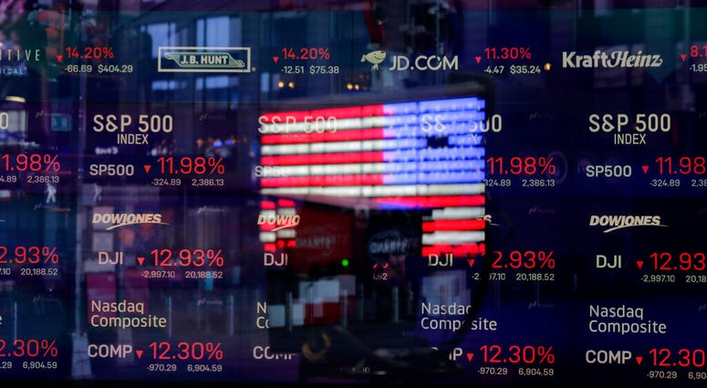 In this March 16, 2020 file photo, a United States flag is reflected in the window of the Nasdaq studio, which displays indices and stocks down, in Times Square, New York. (AP Photo/Seth Wenig, File)