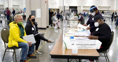 FILE - In this Nov. 20, 2020, file photo, election workers, right, verify ballots as recount observers, left, watch during a Milwaukee hand recount of presidential votes at the Wisconsin Center in Milwaukee. (AP Photo/Nam Y. Huh File)