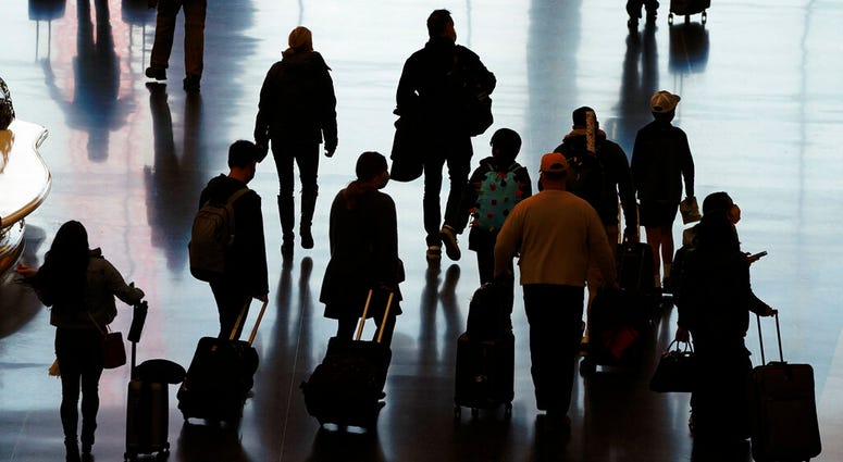 In this Wednesday, Nov. 25, 2020 file photo, travelers walk through the Salt Lake City International Airport in Salt Lake City, a day before Thanksgiving. (AP Photo/Rick Bowmer)