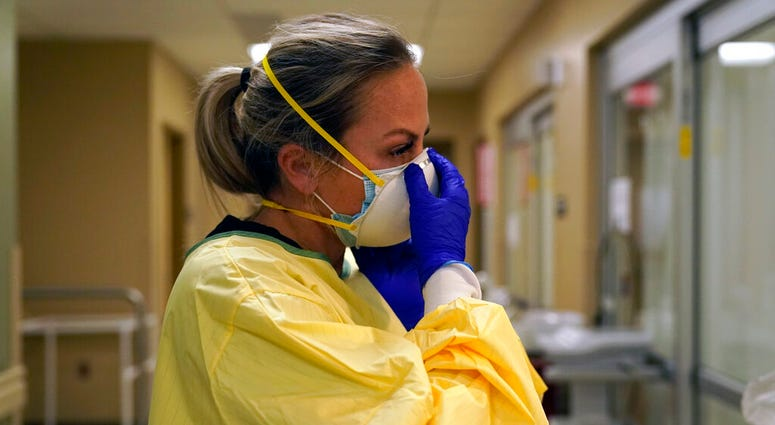 In this Nov. 24, 2020, file photo, registered nurse Chrissie Burkhiser puts on personal protective equipment as she prepares to treat a COVID-19 patient in the emergency room at Scotland County Hospital in Memphis, Mo. (AP Photo/Jeff Roberson, File)