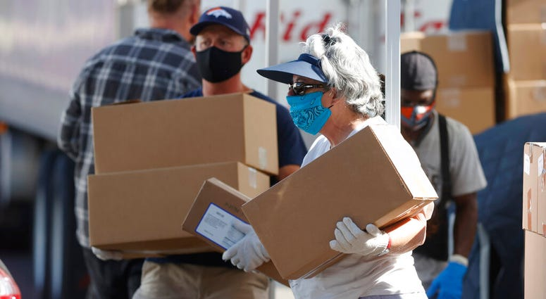 FILE - In this June 26, 2020, file photo, volunteers Juanita MacKenzie, front, and Dave Stutman carry boxes of food to a waiting car at a large mobile pantry set up by the Food Bank of the Rockies. (AP Photo/David Zalubowski, File)