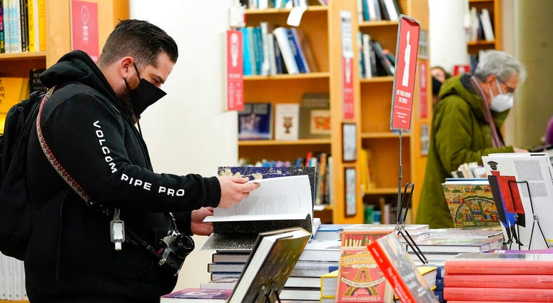 In this Saturday, Nov. 28, 2020, file photo, customers browse while shopping for books at the Strand Bookstore, an independent family owned bookstore founded in 1927 in New York. (AP Photo/Mary Altaffer)