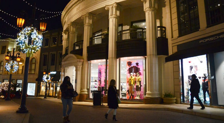 People walk near the Versace boutique on Rodeo Drive, decorated for the holidays amid the coronavirus pandemic, Monday, Nov. 30, 2020, in Beverly Hills, Calif. (AP Photo/Pamela Hassell)