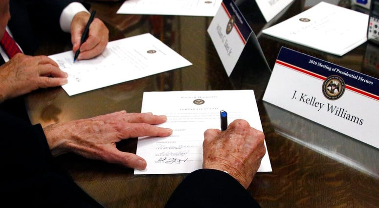 FILE - In this Dec. 19, 2016, file photo members of the Mississippi Electoral College sign certificates of vote in the process of formally casting their electoral votes in the 2016 General Election