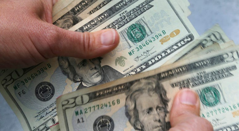 FILE - In this June 15, 2018, file photo, 20-dollar bills are counted in North Andover, Mass.